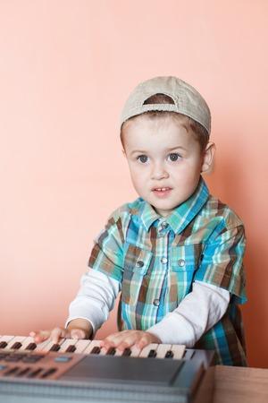 Portrait of a pretty boy wearing baseball cap backwards playing the digital piano
