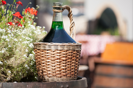 Large Vintage Wine Bottles in wicker basket on a barrel. Autumn still life with a bottle of wine and flowers