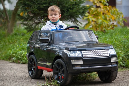 Cute boy in riding a black electric car in the park. Funny boy rides on a toy electric car