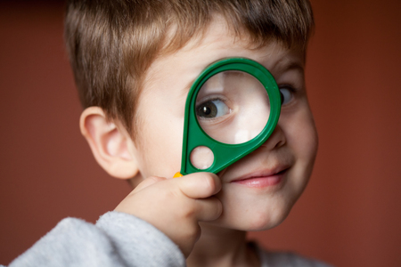 Funny boy looking through magnifying glass with surprise. Closeup Portrait Pretty Boy