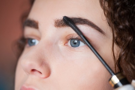 Young woman undergoing eyebrow correction procedure. Beauty and makeup concep