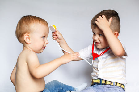 Children playing doctor and patient. Two little boys using stethoscope. Check the heartbeat. Kids play doctor Stock Photo