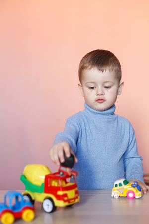 A cute little boy playing with model car collection. Toy mess in child room. Educational games for kids. Stockfoto