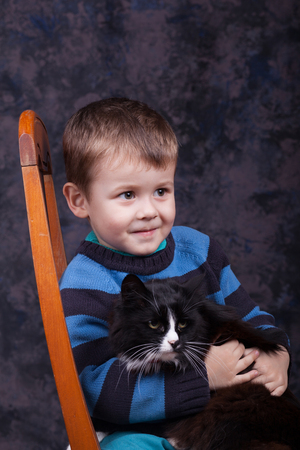 Little boy holding a black cat. Boy and kitten. Reklamní fotografie