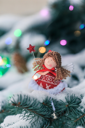 Angel on a fir-tree branch in thesnow-covered wood. Christmas background.