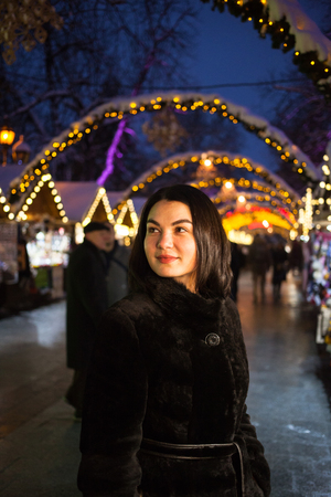 Pretty brunette posing at Christmas Holiday market in Lviv, Ukraine, with light decorations in background. High ISO. Outdoor photo
