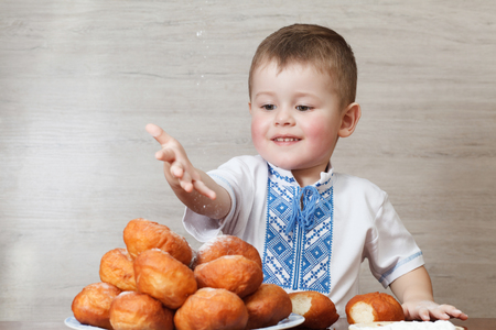 Cute boy embroidered shirt eating donuts. Tasty food for kids. Stock Photo