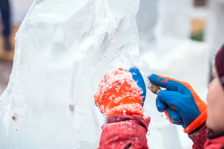 Master makes ice sculptures from ice. The sculptor cuts ice contours from ice with a chainsaw Banque d'images