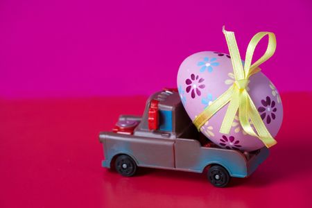 Pickup toy carrying one decorated easter egg. Easter holiday concept