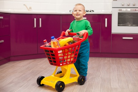 Cheerful little boy with shopping cart. Kid plays in the kitchen. Boy and shopping. Little kid in casual wear carrying child plastic shopping trolley. Shopping, discount, sale concept Banque d'images