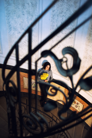 Young beautiful woman standing on old round spiral staircase. Top view. Girl Holds Bright Daffodils Hands