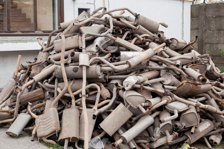 Close view pile of used mufflers at car workshop. Old car mufflers. Lot of exhaust pipes stacked in absolutely no order 版權商用圖片