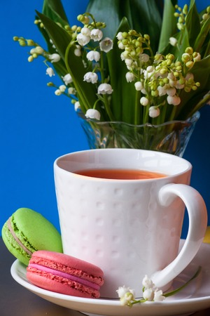 French multicolored cakes macarons and a cup of tea. A bouquet of lily of the valley in a crystal vase. Concept spring holiday, congratulations background 写真素材