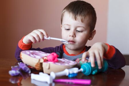 Cute little boy playing with many-colored plasticine. Boy playing with toys Dental Tools. Facial expression. Children creativity.