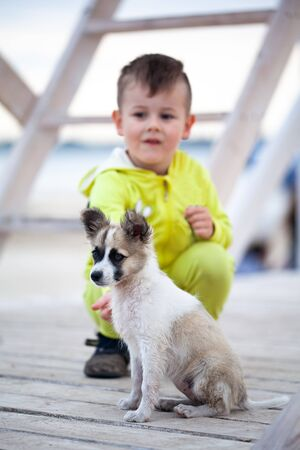 Cute little boy with his puppy. Protection of animals. Child and his best four-legged friend