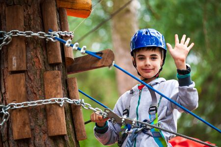 Young boy climbing pass obstacles in rope. Child in forest adventure park. Kids climb on high rope trail. Agility and climbing outdoor amusement center for children.