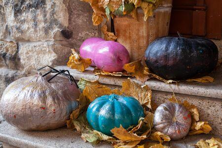 Halloween verzierte Haustür mit verschiedenen Farb- und Formkürbissen.