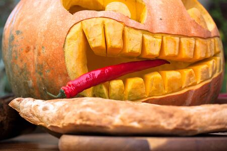 Hungry pumpkin with pepper. In mouth a pointy red pepper tongue sticks out between crooked tip teeth. Imagens