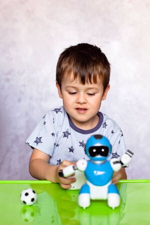 Little boy is playing with robot. Robot for children. Kids and toys. Smart toy