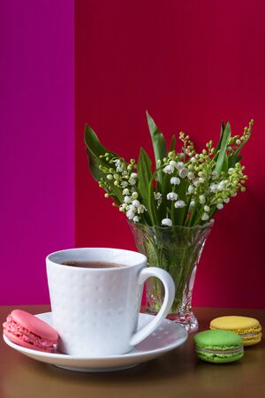 French multicolored cakes macarons and a cup of tea. A bouquet of lily of the valley in a crystal vase. Concept spring holiday, congratulations background
