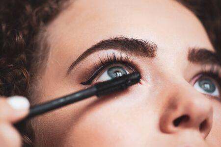 Closeup of makeup artist applying smokey eyes makeup. Beauty and makeup concept
