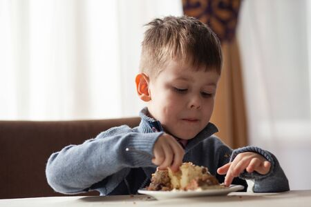 Cute little boy in cafe eat a big piece of cake with a fork. Desserts for kids. He is enjoying it.
