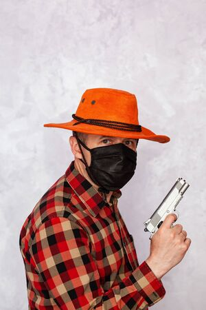 Portrait of a cowboy with a mask and a gun. American bandit in mask, western man with hat. Stockfoto
