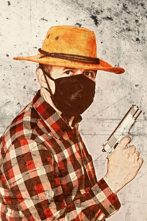 Portrait of a cowboy with a mask and a gun. Edited with a vintage film effect. American bandit in mask, western man with hat.