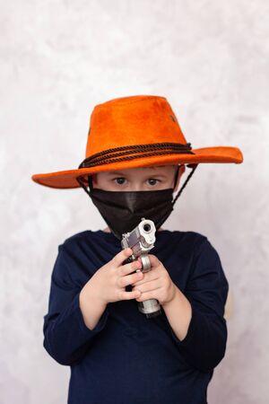 Child cowboy with a gun. Caucasian little boy with cowboy hat.