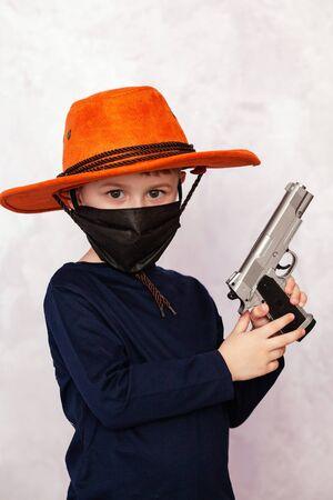 Caucasian little boy with cowboy hat. Child cowboy with a gun. Stock Photo