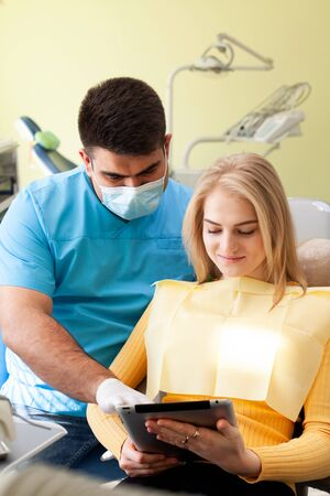 The dentist showing teeth x-ray to the patient on tablet, explaining the problem using smart technology. Zdjęcie Seryjne