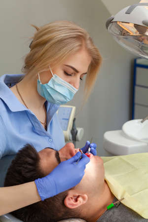 Man visiting female dentist at clinic. Young man sitting mouth wide open at the office of dentist at the annual examination. Doctor girl