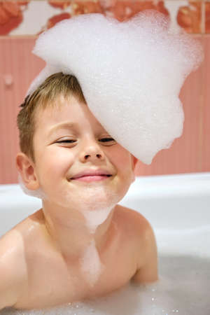 Portrait of a smiling child in the bath with his head full of foam. Happy bathing baby with foam on his head