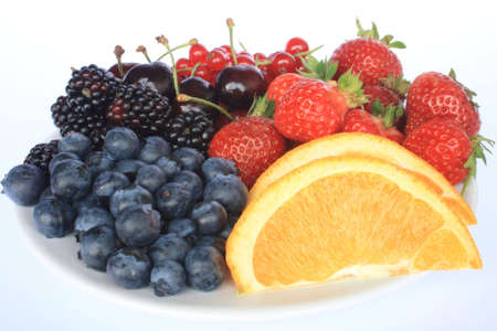 Berries and an orange on a plate photo