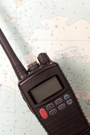 A marine vhf radio lying on an old chart