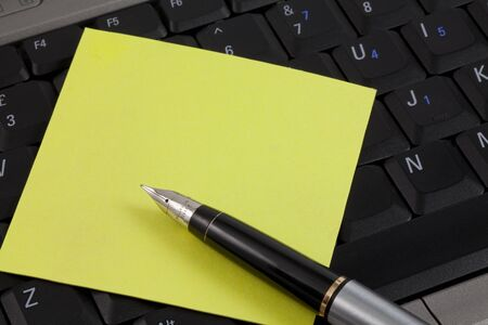 A yellow post it note and a fountain pen on a laptop keyboard. With copy space. photo
