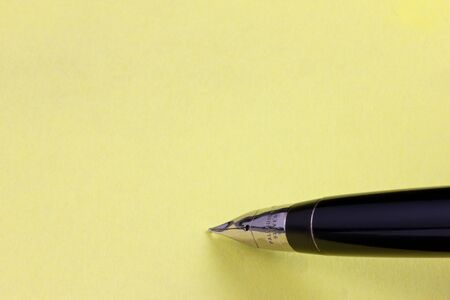 Fountain pen on a yellow post-it with copy space photo