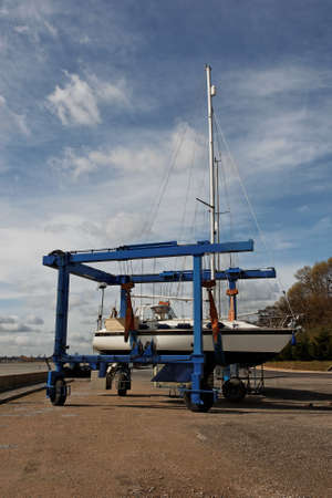boat lift: A sailing yacht being transported in a boat lift in a boatyard