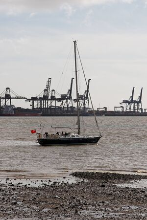 felixstowe: A sailing yacht aground in Harwich Harbour, UK with Felixstowe Container Terminal in the background