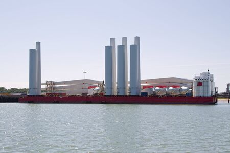 A semi-submersible barge loaded with wind farm turbines,in harbour in the UK photo