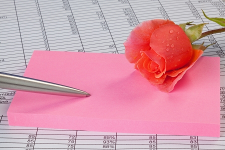 A rose, notepad and pen on a spreadsheet photo