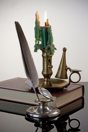 Antique inkwell and quill pen with a brass candlestick and red book - white vignette background photo