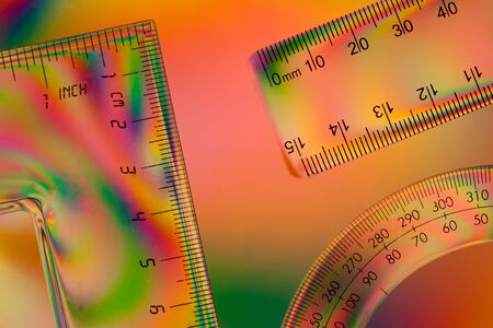 polarised: Scales on a ruler,set square and protractor against a colourful double polarised background