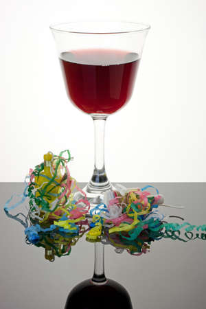 party poppers: Glass of red wine with party poppers and streamers Stock Photo