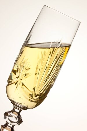 A tilted glass of vintage champagne - toasting Stock Photo