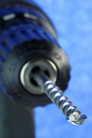 Electric drill and bit in close-up with shallow depth of field  36 mp image against blue  Logos removed photo