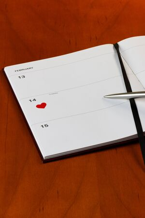 Generic diary on a desktop with a heart symbol on St.Valentines Day. With copy-space and pen photo