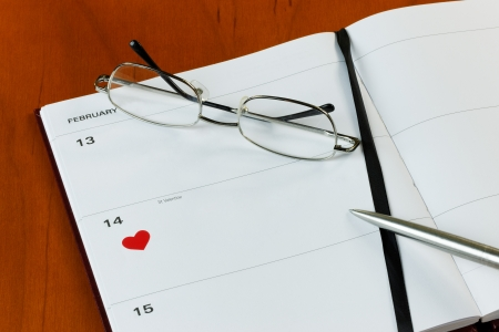 Generic diary on a desktop with a heart symbol on St.Valentines Day. With copy-space , pen and glasses photo