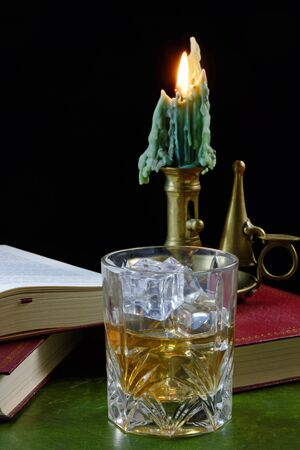 A glass of whisky with ice standing on an antique book, with candle - text in book not subject to copyright photo