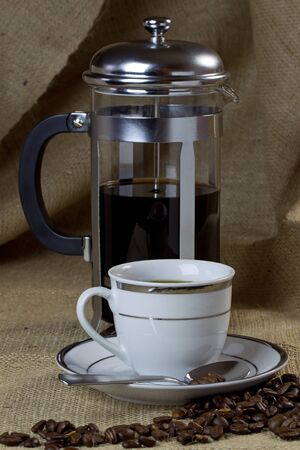 coffee pot: A cup of coffee on hessian with a cafetiere and beans